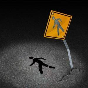 Traffic accident injury concept as a damaged road sign with a person pedestrian symbol fallen on the floor with broken bones and physical pain after a car crash as a metaphor for accident insurance or drunk driving dangers.